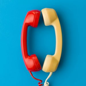 two handsets facing each other and talking on blue background
