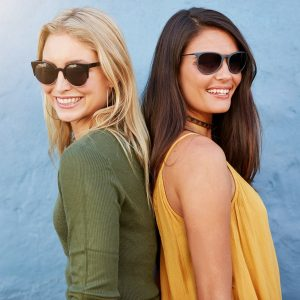 Two women smiling back to back. Stylish female friends wearing sunglasses looking at camera against blue background.